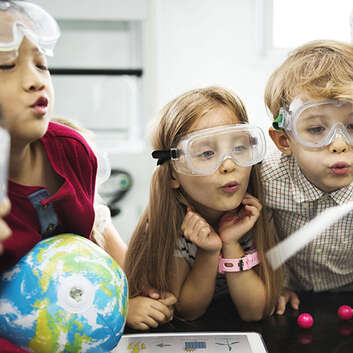 Young children watching a physics activity