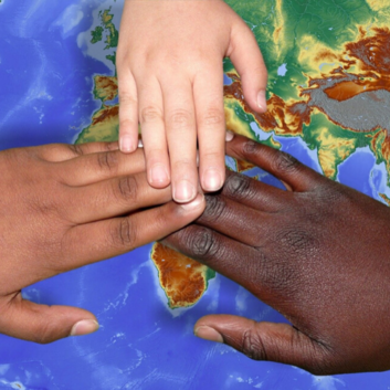 Three hands with different skin colour overlaying each other across a map of the world.