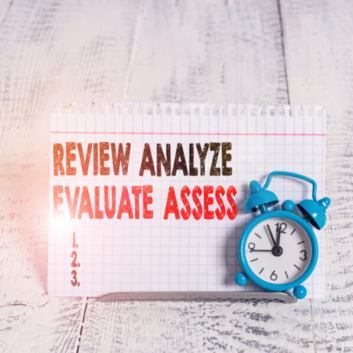 Image says; review, analyse, evaluate, assess with a blue alarm clock.