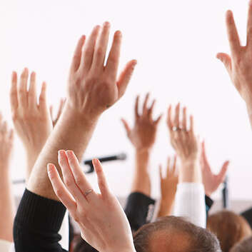 People raising hands at AGM