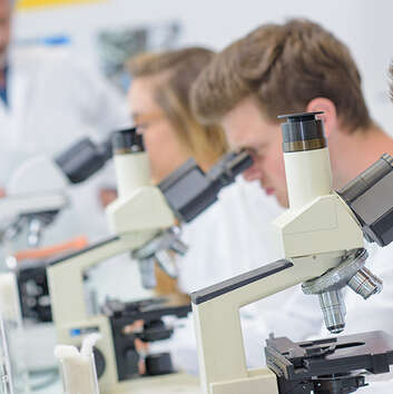 University students using microscopes in a physics laboratory